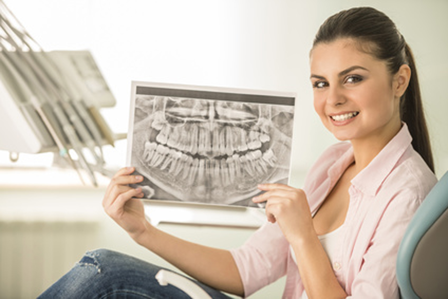 Portrait of mid adult brunette female patient with x-ray her teeth in dentistry.
